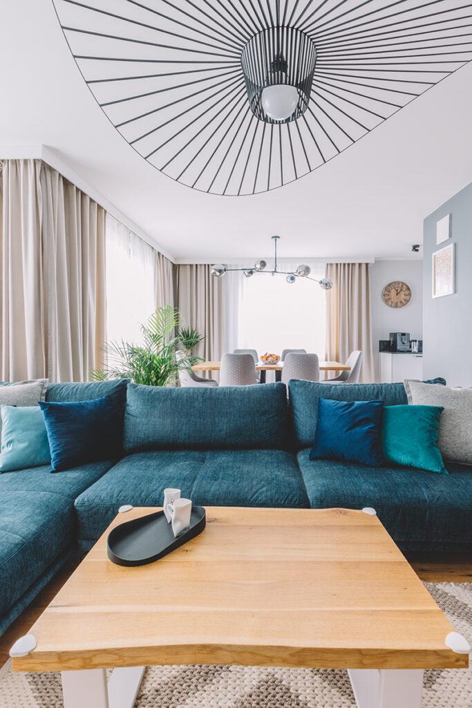 dnevni-boravak-plava-sofa-luster-zavjese-domnakvadrat
